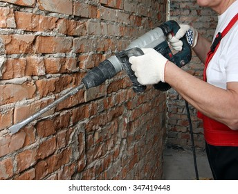 House-builder in uniform and red helmet working with a plugger against the brick wall