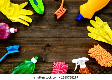 Housecleaner tools set with detergents, soap, cleaners and brush on wooden background top view mock up