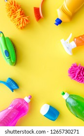 Housecleaner tools set with detergents, soap, cleaners and brush on yellow background top view mock up