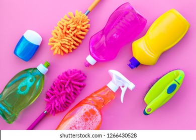 Housecleaner tools set with detergents, soap, cleaners and brush on pink background top view mock up