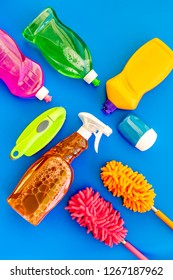 Housecleaner tools set with detergents, soap, cleaners and brush on blue background top view mock up