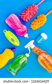 Housecleaning with detergents, soap, cleaners and brush in plastic bottles on blue background top view mockup
