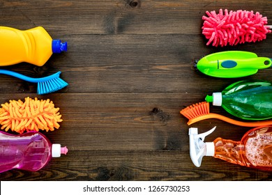 Housecleaning with detergents, soap, cleaners and brush in plastic bottles on wooden background top view mockup