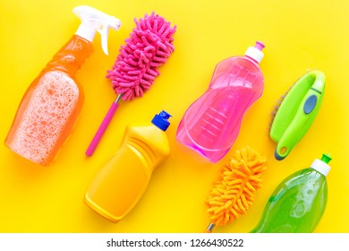 Housecleaning with detergents, soap, cleaners and brush in plastic bottles on yellow background top view mockup