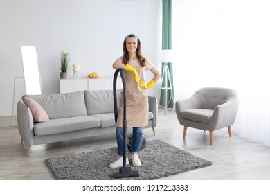 Housecleaning service. Happy young maid with vacuum cleaner standing in middle of tidy living room, full length portrait. Positive millennial housewife doing domestic chores, copy space
