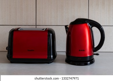 Household appliances: bright stylish red & black modern electric toaster and a kettle on a beige kitchen counter