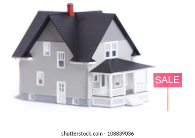 Household architectural model with sale sign, isolated on white