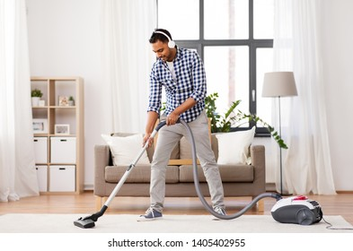 household and cleaning concept - indian man in headphones with vacuum cleaner at home