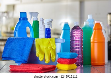 Household cleaning items in basket on kitchen table with blurred background