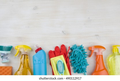 Household cleaning products on wooden background with copyspace at top