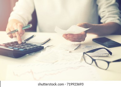 household expenses - woman calculating bills at home