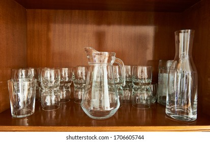 household glassware inside a cupboard with glasses and glass jugs