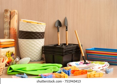 Household goods for the garden. Rubber gloves, flower pots, seedling boxes, rakes, scapula are garden accessories. Household items are collected in a heap.