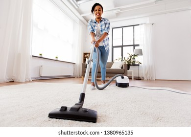 household, housework and cleaning concept - happy african american woman or housewife with vacuum cleaner at home