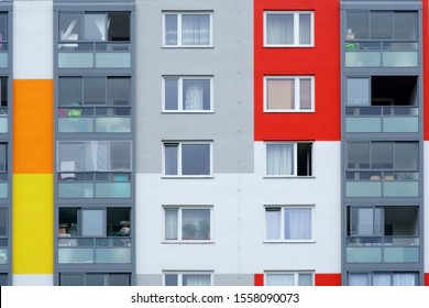 Household items are behind the windows of a multi-storey residential building.