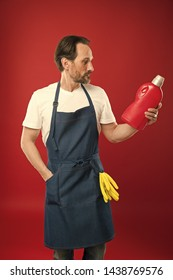 Household laundering. Senior man in apron ready for doing laundry. Mature man holding detergent bottle in hands. Eldery household worker wearing bib apron with rubber gloves. Keeping clothes spotless.