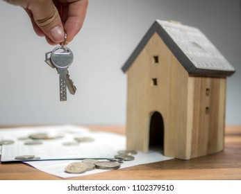 Household savings and finances, Hand holding the key with model house. Saving money concept, real estate and property concept