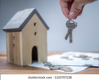 Household savings and finances, Hand holding the key with house model. Saving money concept, real estate and property concept