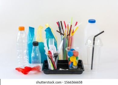 Household single use plastic items including water bottles, caps, net, bags, cups, forks, spoons, knife, coffee stirrers, cotton buds, straws and food tray on white background.