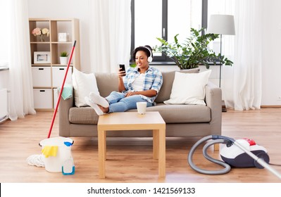 household and technology concept - happy african american woman or housewife in headphones with smartphone resting after home cleaning, listening to music and singing