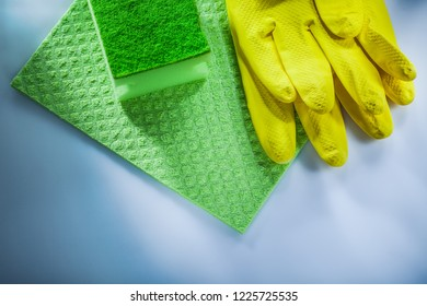 Household washcloth sponge safety gloves on white surface.