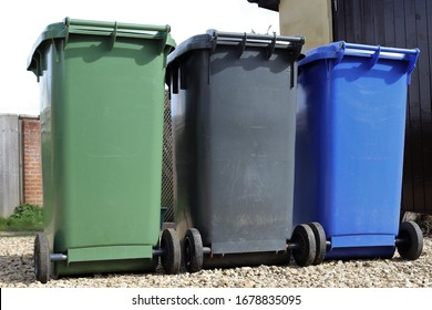 Household waste recycling sheme wheelie bins in Northamptonshire, England. Black for landfill, blue for recyclables and green for garden waste.