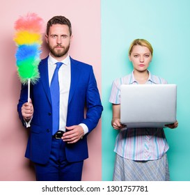 Househusband and female boss. Businessman and housewife. Family couple. Husband stand with dust brush while wife holding laptop. Couple of handsome man and pretty woman. Housekeeping or business.