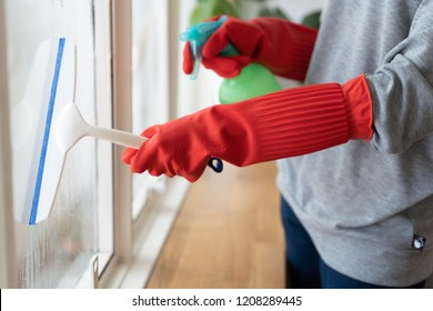 Housekeeper cleaning home concept. Woman spraying cleanser to window.