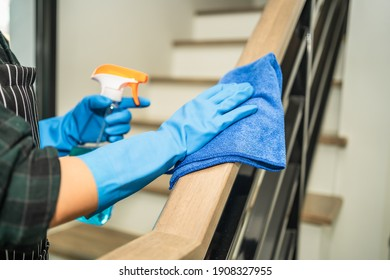 Housekeeper cleaning railing by using alcohol and liquid cleaning solution, disinfection and hygiene concept.