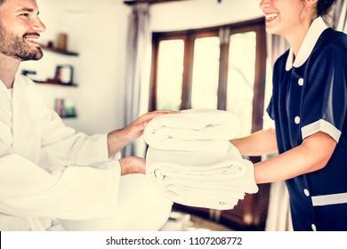 Housekeeper handing over fresh towels