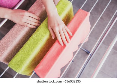 The housekeeper hangs up the laundry after washing. Home life. Female hands hang washed clothes on the dryer. Women's hands and wet clothes