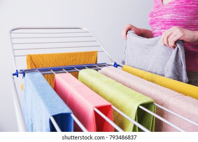 The housekeeper hangs up the laundry after washing. Home life. Female hands hang washed clothes on the dryer. Women's hands and wet clothes. A woman hangs up wet clothes after washing.
