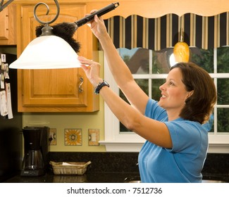 Housekeeper / maid using a feather duster to clean a lamp in a kitchen with black granite counter tops in the background.