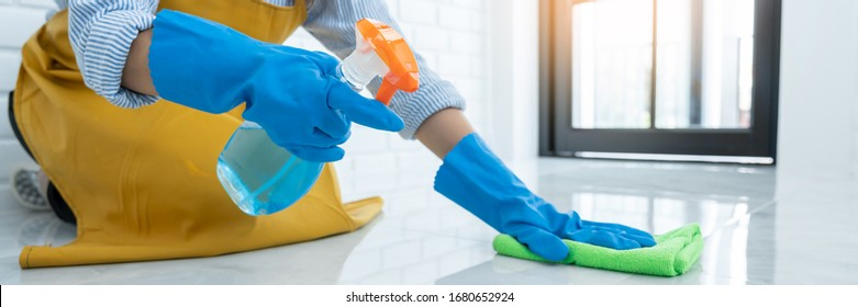 Housekeeper maid wearing rubber gloves with cloth cleaning or applying floor care and cleaners at home, housework and housekeeping concept