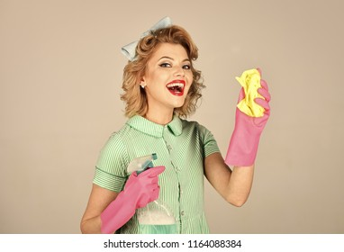 Housekeeper in uniform with clean spray, duster. Cleaning, retro style, purity. Pinup woman hold soup bottle, duster. Retro woman cleaner on grey background. Cleanup, cleaning services, wife, gender