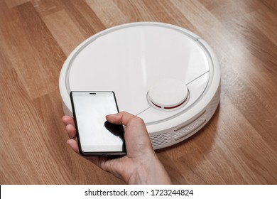 housekeeper using mobile to control black robotic vacuum cleaner. modern smart cleaning technology housekeeping.