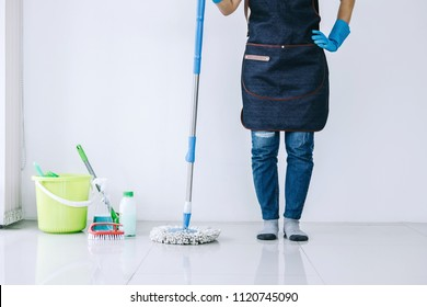 Housekeeping and cleaning concept, Happy young woman in blue rubber gloves wiping dust using mop while cleaning on floor at home.