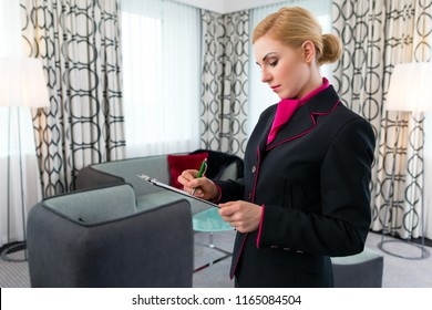 Housekeeping manager or assistant controlling hotel suit or suit with checklist on tidiness