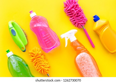 Housekeeping set. Detergents, soap, cleaners and brush for housecleaning on yellow background top view mock-up