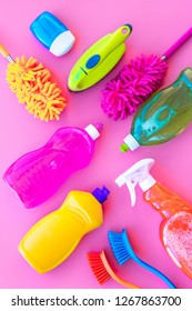 Housekeeping set. Detergents, soap, cleaners and brush for housecleaning on pink background top view mock-up