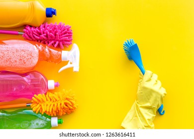 Housekeeping tool. Detergents, soap, cleaners and brush for housecleaner work on yellow background top view space for text