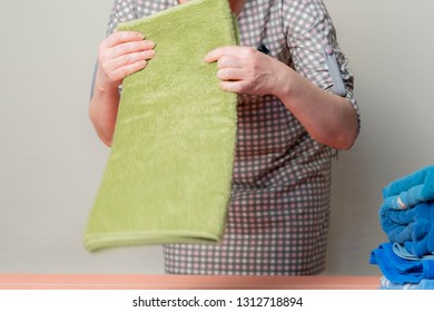 housemaid folding towels in hotel room