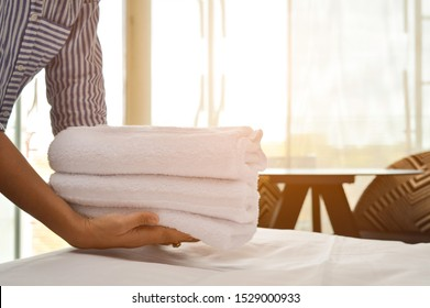 Housemaid hands holding a stack of fresh white bath towels on the bed sheet. Housekeeper service cleaning in the hotel room. Concept about lifestyle, holiday, travel and person.