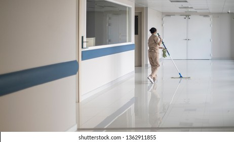 Housemaid using the mop in hospital walkway to cleaning the white floor with reflection.
