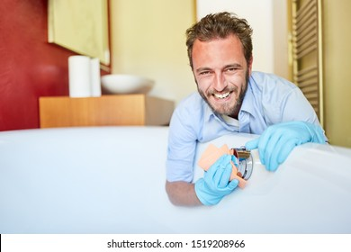 Houseman with cleaning rag cleaning the bathtub during spring cleaning