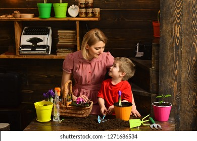 Houseplant concept. Little son help mother with houseplant. Child and mother planting houseplant in potting soil. Houseplant care.