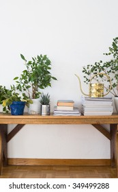 Houseplants, books, pile of journals and watering can arranged on the wooden bench