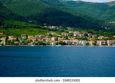 Houses along the sea in the background of mountains