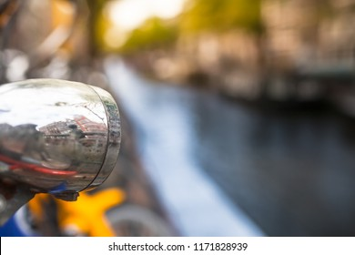 Houses of Amsterdam reflect at old bicycle lamp with typic blurred city background of waterway canal and buildings (copy space)