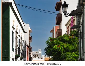 Houses with balconies in the streets of Santa Cruz de La Palma, Spain, with blue sky.